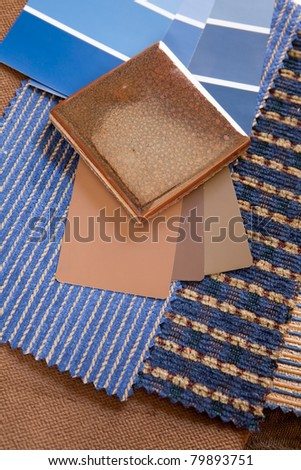 Blue and brown paint color and fabric swatches with a ceramic floor tile - stock photo