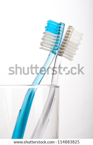 Blue and Clear tooth brush in glass Isolated on white background - stock photo