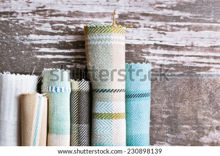 Blue and cream tartan fabric rolls - stock photo