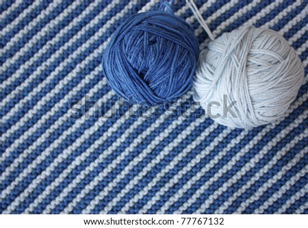 Blue and dark blue balls against a knitted cloth