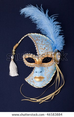 blue and gold feathered mask isolated on a black background