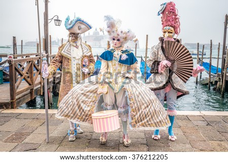 Blue and gold masked carnival costumes trio, Venice, Italy. - stock photo