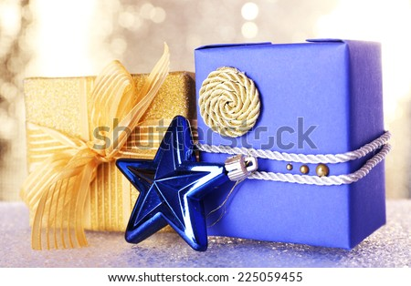 Blue and golden gift boxes and Christmas toy on table on shiny background - stock photo