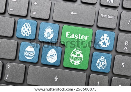 Blue and green easter egg on keyboard - stock photo