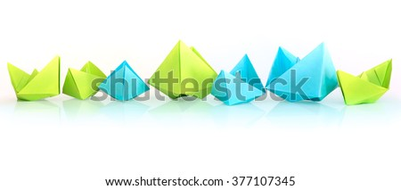Blue and green folded paper ships on white background - stock photo