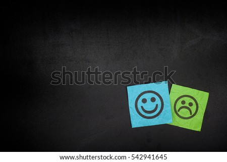 Blue and green paper notes with happy and sad faces on blackboard. Vignette.