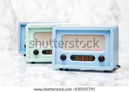 Blue and green radios with retro look on white marble background