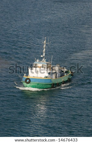 blue and green tugboat leave caribbean dock