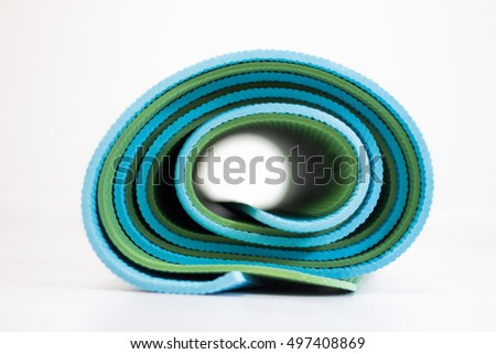 Blue and green yoga mats twisted together
