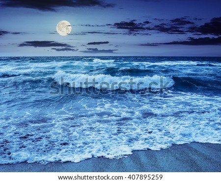 blue and mighty sea wave attacks the sandy beach and break on them at night in full moon light