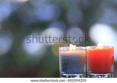 blue and orange candle in small glasses light point and white bokeh on green background