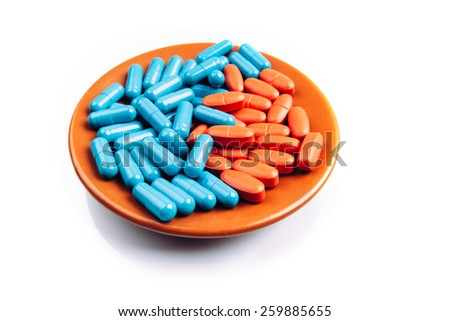 Blue and orange pills on the plate isolated on white