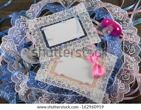 Blue and pink greeting cards with pacifiers on wooden background - stock photo