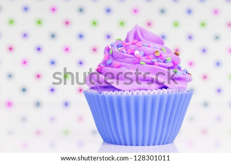 Blue and purple cupcake with whipped cream and sprinkles on a dotted background