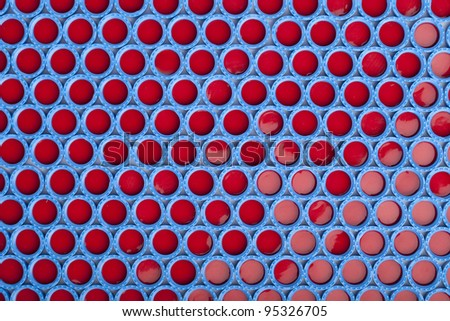 Blue and red carved plastic caps for chromatographic vials. Background, texture, pattern. - Please see my portfolio for similar images - stock photo