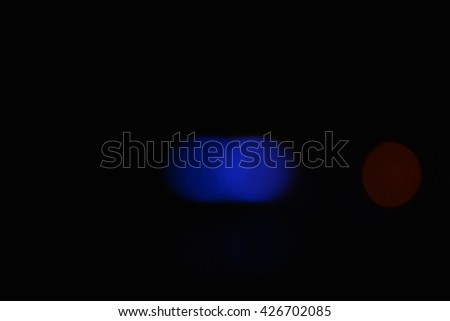 Blue and red defocused blurry circular night city lights glowing soft in the darkness. They soothe, brings a positive and located in the center of the photo. - stock photo