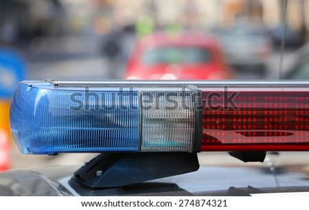 Blue and red flashing sirens of police car during the roadblock in the city - stock photo