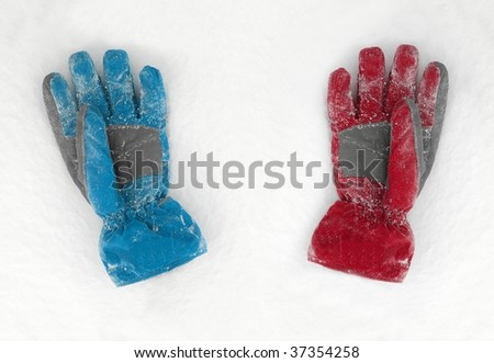 Blue and red gloves lieing on the snow - stock photo