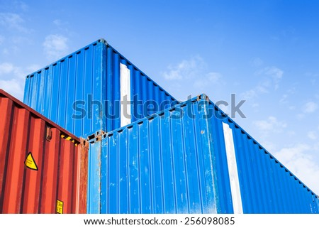 Blue and red metal industrial cargo containers are stacked in the storage area under blue cloudy sky - stock photo