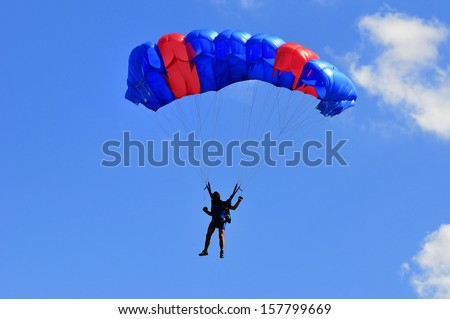 Blue and red sail parachute on blue sky