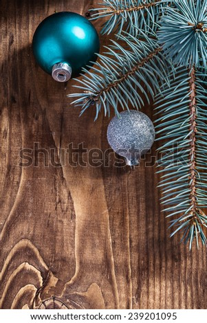 blue and silver christmas balls and pinetree branch on old wooden board with copyspace - stock photo