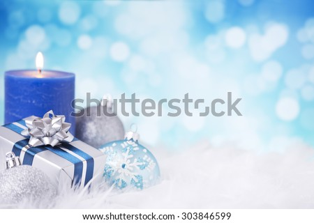 Blue and silver Christmas baubles, a gift and a candle on a soft feathery surface in front of defocused blue and white lights. - stock photo