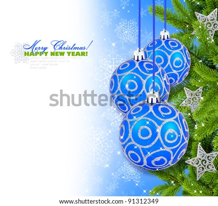 Blue and silver christmas decoration baubles and pine on blue background with space for text - stock photo