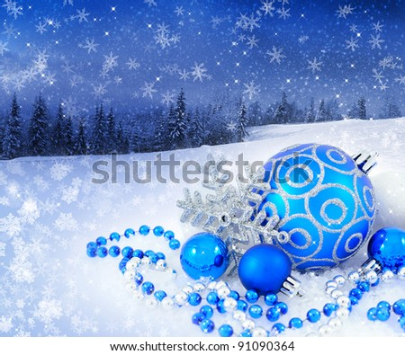 Blue and silver christmas decoration baubles on a background a winter landscape - stock photo