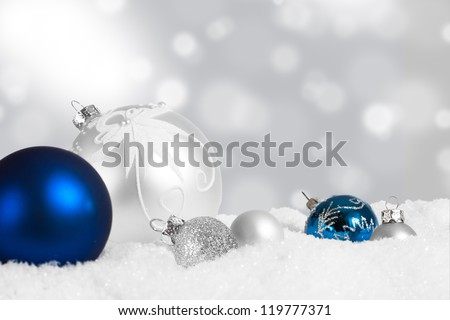 Blue and silver ornaments in snow with twinkling lights in background - stock photo