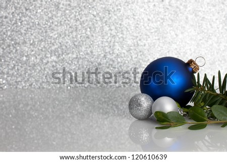Blue and Silver ornaments with evergreens on glittery background