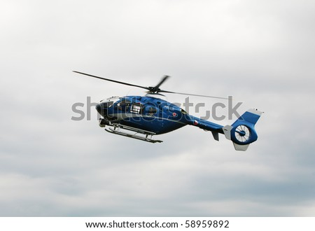 Blue and silver police helicopter flying above - stock photo