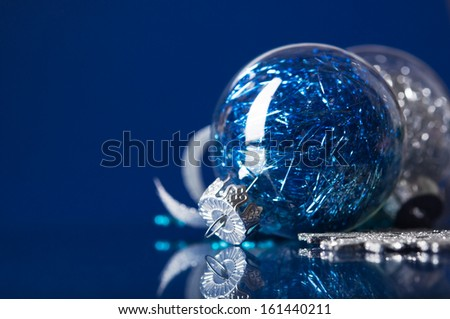 Blue and silver xmas ornaments on dark blue background with space for text - stock photo