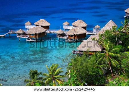 Blue and turquoise lagoon and bungalows in Bora Bora, French Polynesia - stock photo