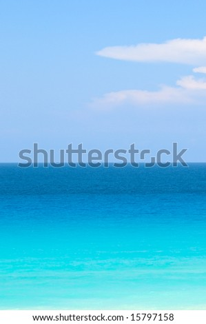 Blue and turquoise tropical ocean under bright blue sky - stock photo