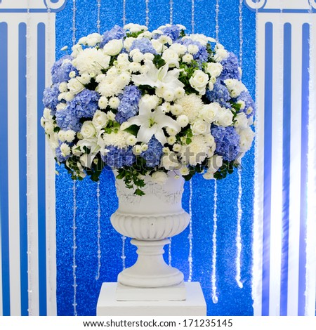blue and white and green flowers in ceramic pot - stock photo