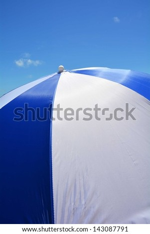 Blue and white beach umbrella, perfect for cover art - stock photo