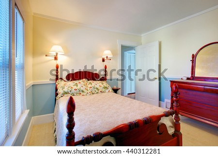 Blue and white bedroom interior with high pole carved wood bed and brown cabinet with mirror.