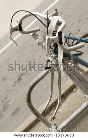 Blue and white bullhorn bicycle without front tire.