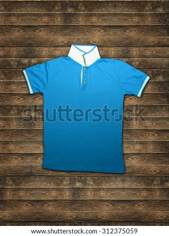 blue and white color t-shirt with collar on wood background - stock photo