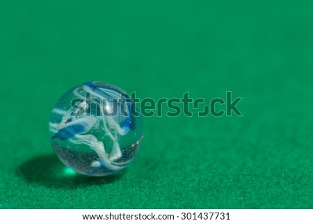 Blue and white Colorful Marble Ball on Green background - stock photo