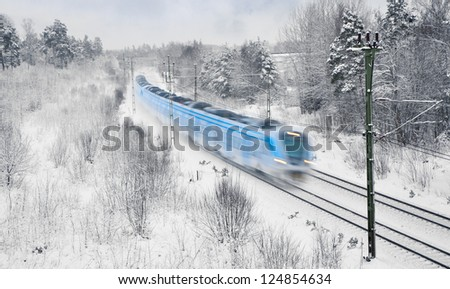 Blue and white commuter train in blurred motion in snow