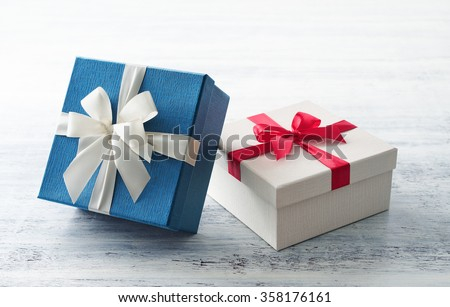 Blue and white gift box with ribbon on white painted wood background  - stock photo