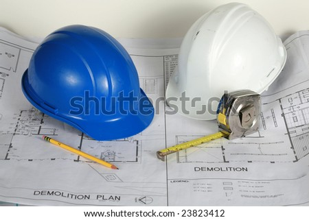 blue and white hard hats on blue prints - stock photo