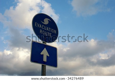 blue and white hurricane evacuation route signs against a cloudy sky - stock photo