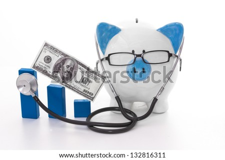 Blue and white piggy bank wearing glasses and stethoscope listening to graph model - stock photo