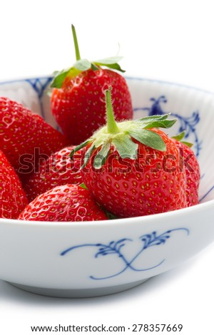 Blue and white porcelain bowl of whole fresh succulent ripe red strawberries with their green stalks attached for a healthy dessert or snack - stock photo