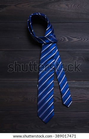 Blue and white striped necktie on black wooden table - stock photo
