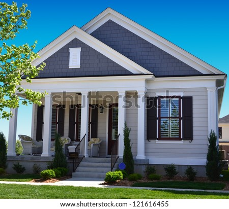Blue and White Suburban American Cape Cod Home with Front Porch - stock photo