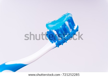 Blue and white tooth brush with shiny blue toothpaste. Isolated white backdrop.
