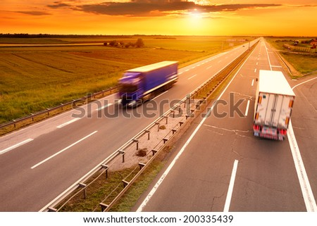 Blue and white truck in motion blur on the highway at sunset - stock photo